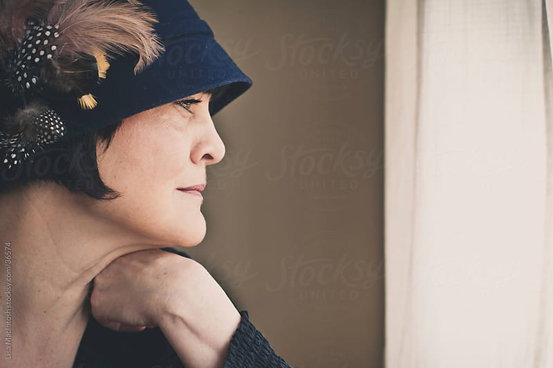 woman wearing vintage blue hat with feathers staring out window by Lisa MacIntosh for Stocksy United