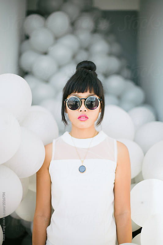 Young fashion woman portrait standing with balloons background by Nabi Tang for Stocksy United