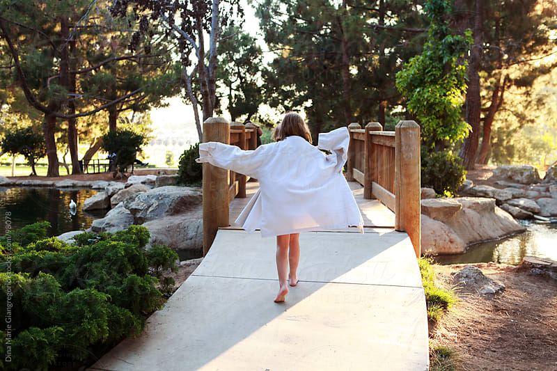 Little girl walking towards bridge wearing oversized white shirt by Dina Giangregorio for Stocksy United