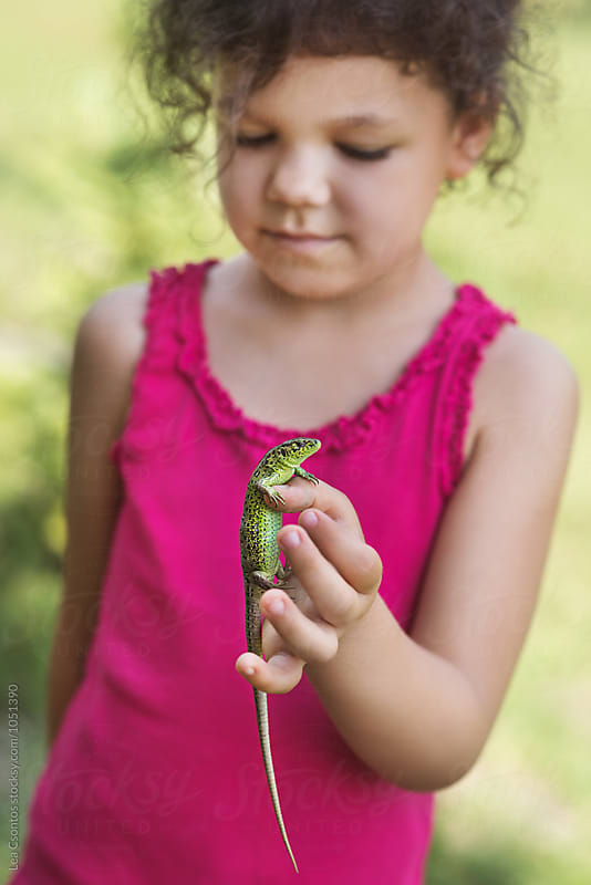 Girl holding a lizard in her hand by Lea Csontos for Stocksy United