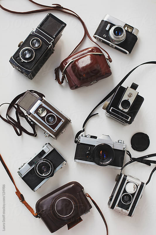 Overhead shot of vintage cameras on white background by Laura Stolfi for Stocksy United