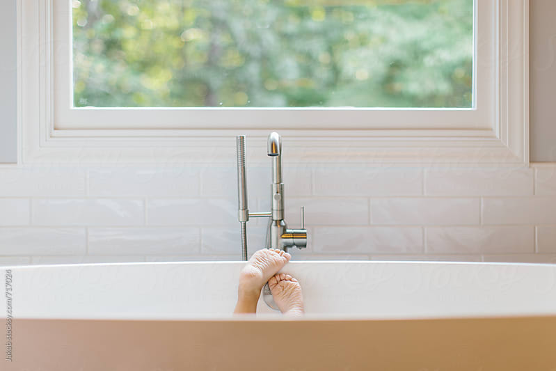 A young girl's feet in a bathtub by Jakob for Stocksy United