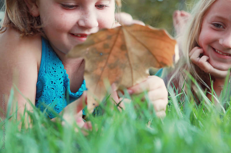 Two Girls Lying In Grass Looking At Large Leaf by Dina Giangregorio for Stocksy United
