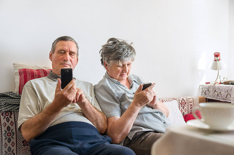 Senior couple using smartphones at home by RG&B Images for Stocksy United