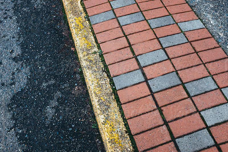 Detail of curb and sidewalk along urban street by Paul Edmondson for Stocksy United