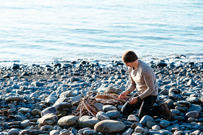 Man building a fire on the beach by Suzi Marshall for Stocksy United