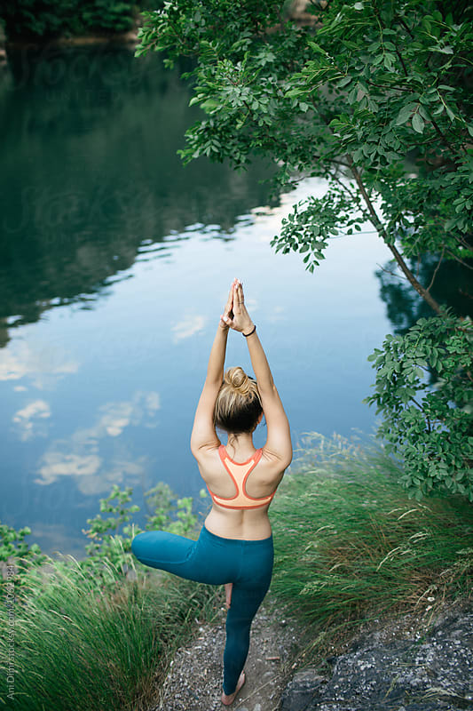 Young woman doing yoga in nature by Ani Dimi for Stocksy United