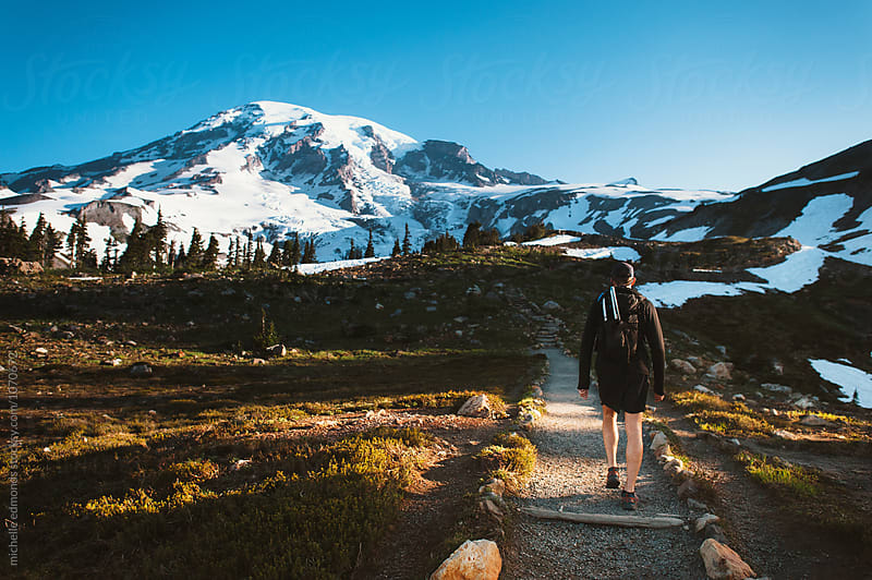 Hiker on a Mount Rainier National Park Trail Facing the Mountain by michelle edmonds for Stocksy United
