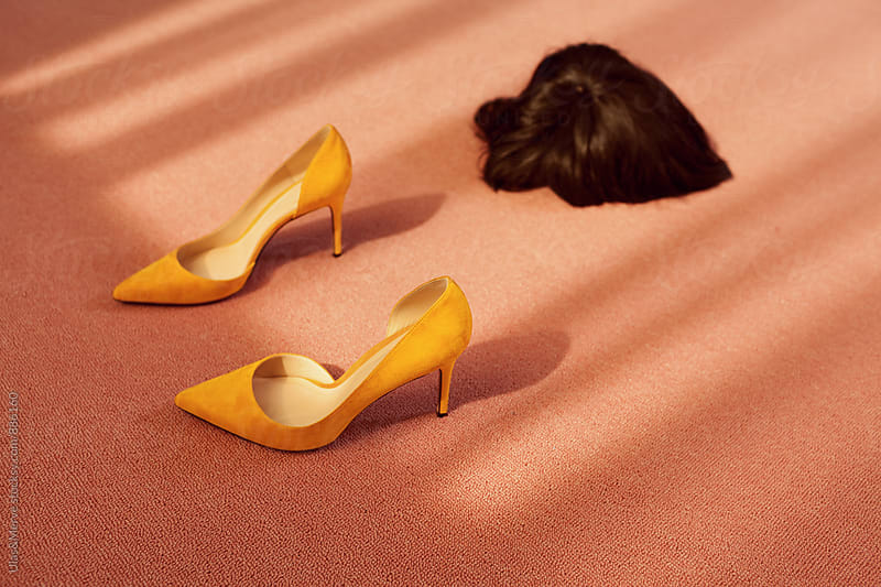 conceptual fashion image with high heels and a wig on pink flooring by Ulaş and Merve for Stocksy United