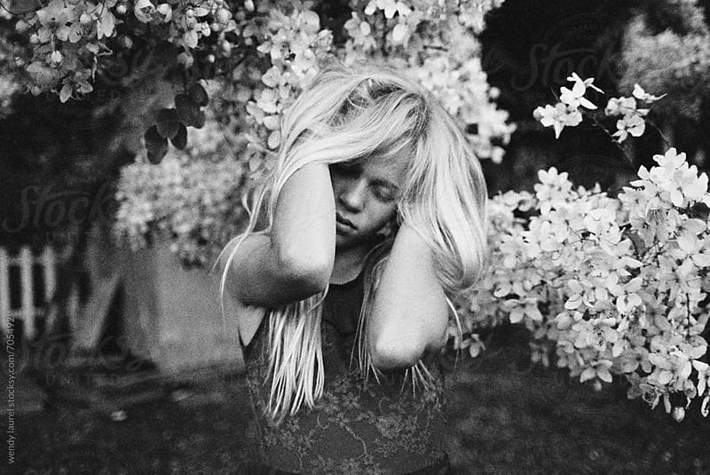 portrait of blonde girl in black and white moody next to flowering tree by wendy laurel for Stocksy United