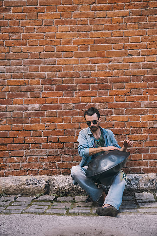 Musician playing handpan in front of the brick wall by Danil Nevsky for Stocksy United