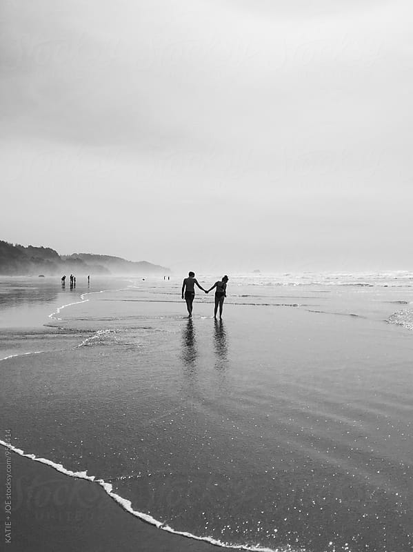 Man and woman holding hands on the beach by KATIE + JOE for Stocksy United