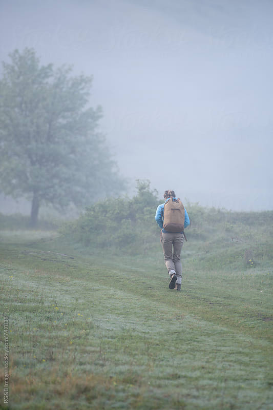 Woman with backpack walking outdoor on a foggy day by RG&B Images for Stocksy United