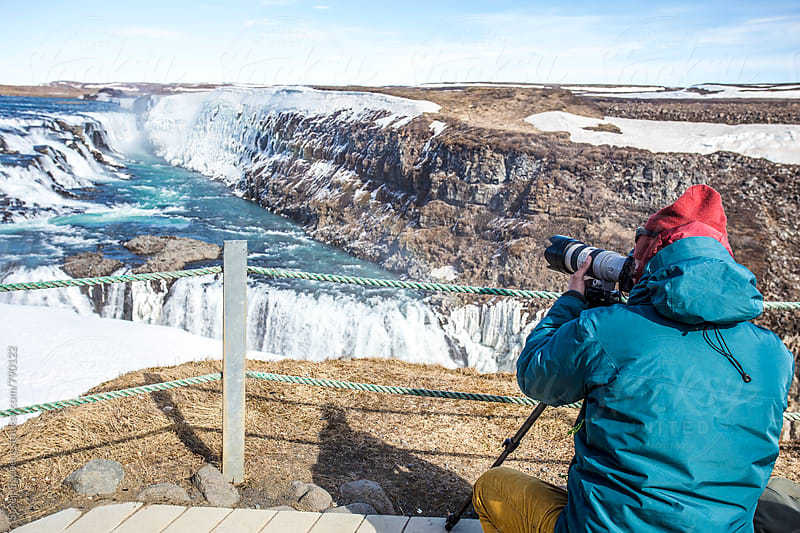 Man taking photos of Gullfoss waterfall in Iceland by Søren Egeberg Photography for Stocksy United