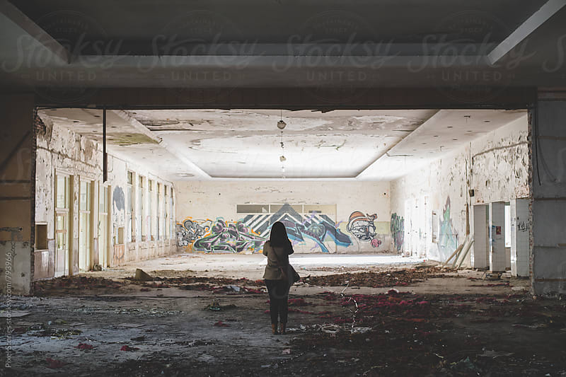 Young woman urban exploring an old building with her camera by Pixel Stories for Stocksy United