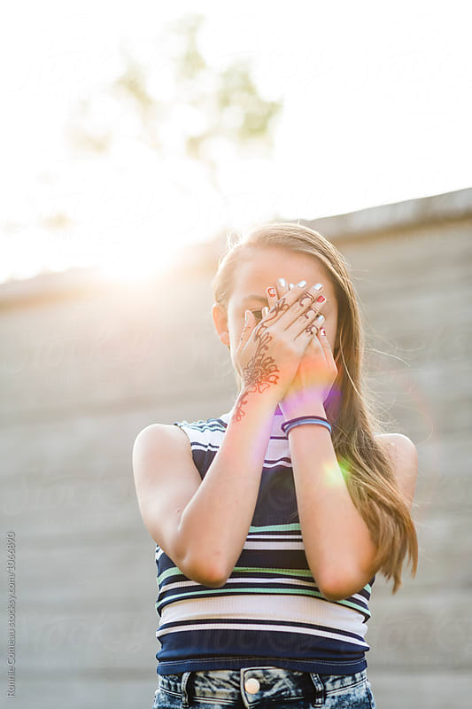 Teen Girl Hiding Face Outdoors In Summer by Ronnie Comeau for Stocksy United