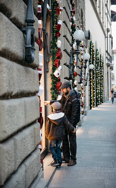 Man and his son looking at the shopping window decorated for Christmas by Beatrix Boros for Stocksy United