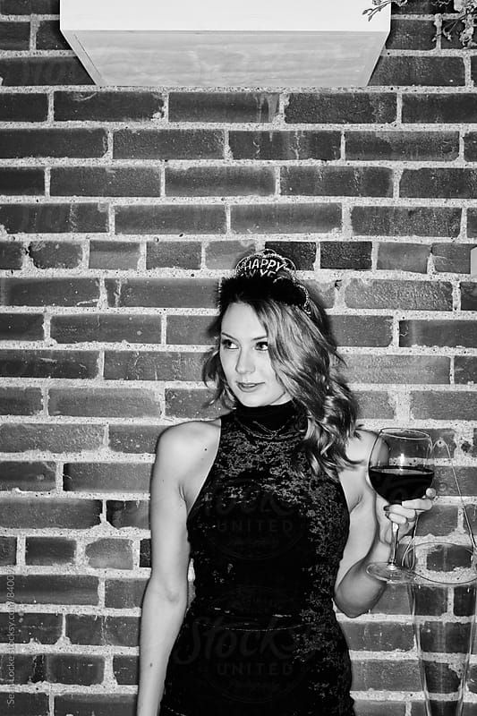 NYE: Woman Stands At Party With Wine Glass by Sean Locke for Stocksy United