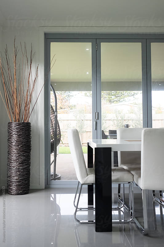 Dining room in modern open plan home by Rowena Naylor for Stocksy United