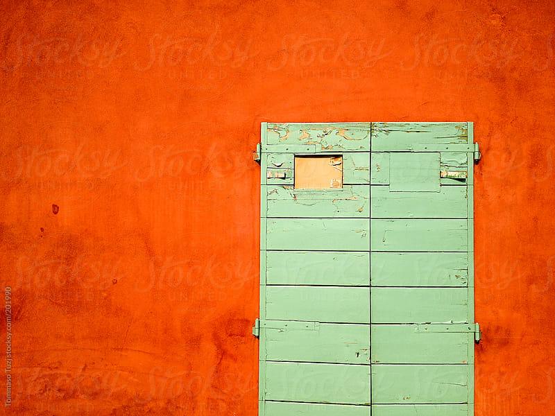 orange wall and green door by Tommaso Tuzj for Stocksy United