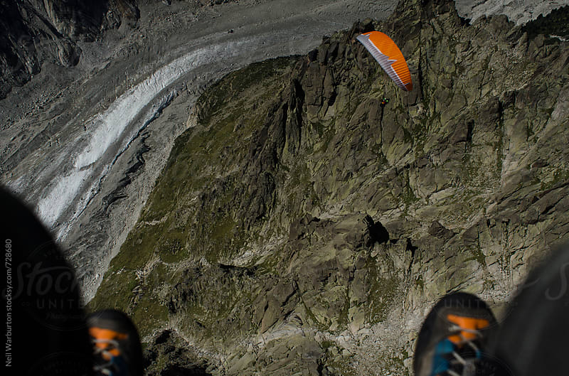 Paragliding over mountain terrain by Neil Warburton for Stocksy United