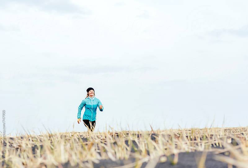 Smiling happy girl running outdoors on the beach by Soren Egeberg for Stocksy United