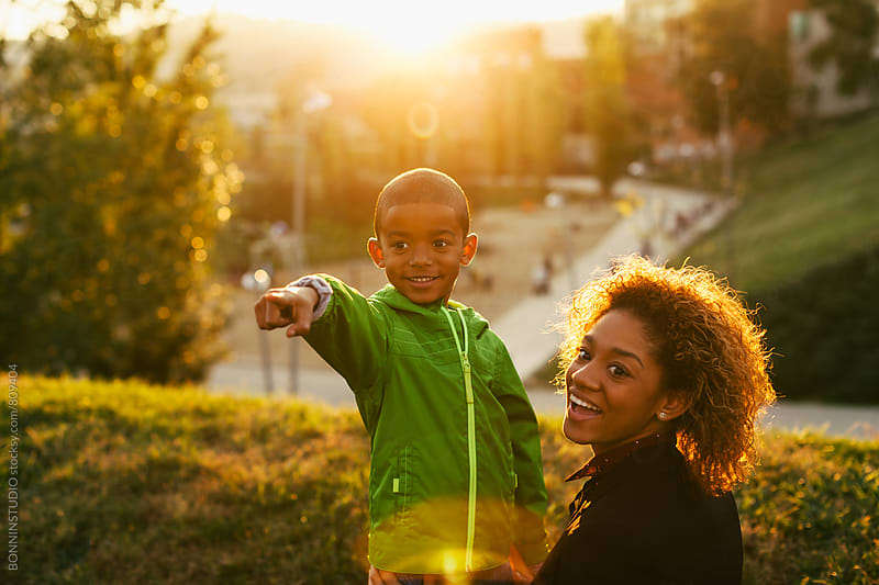 Mother and her son smiling in the park at sunset. by BONNINSTUDIO for Stocksy United