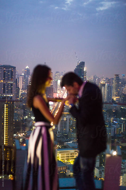 Handsome young man kissing the hand of his beautiful girlfriend during a fun date night in the city  by Jovo Jovanovic for Stocksy United