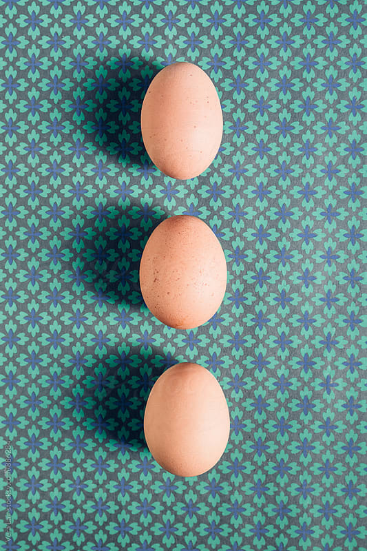 Three eggs on a green and blue pattern by Vera Lair for Stocksy United