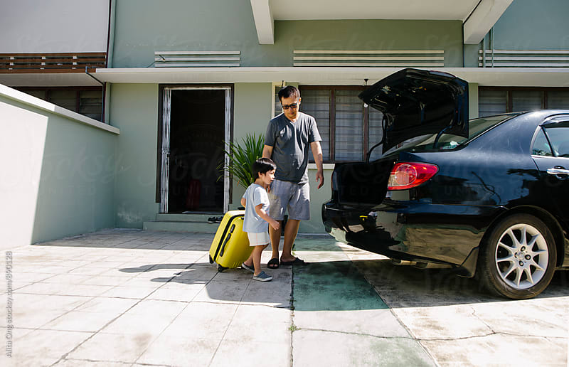 Father and son loading luggage onto a car by Alita Ong for Stocksy United
