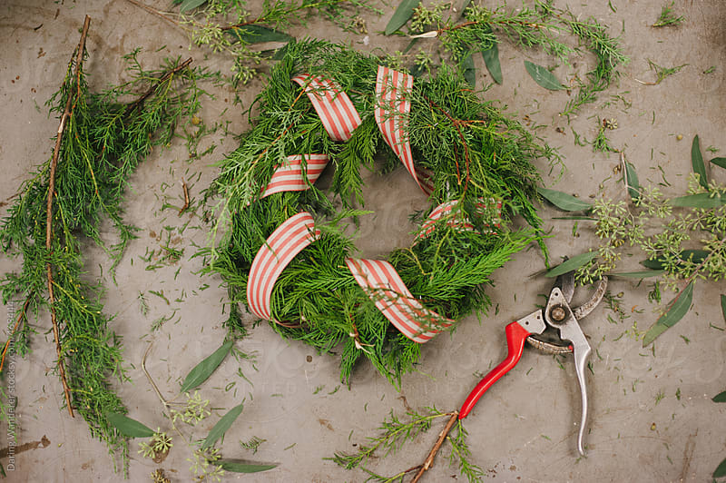 Handmade festive Christmas wreath with red ribbon by Daring Wanderer for Stocksy United