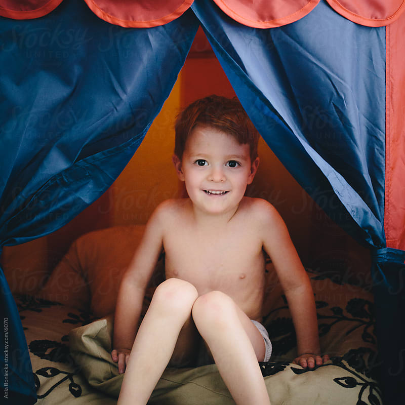 A boy smiling inside his play tent by Ania Boniecka for Stocksy United
