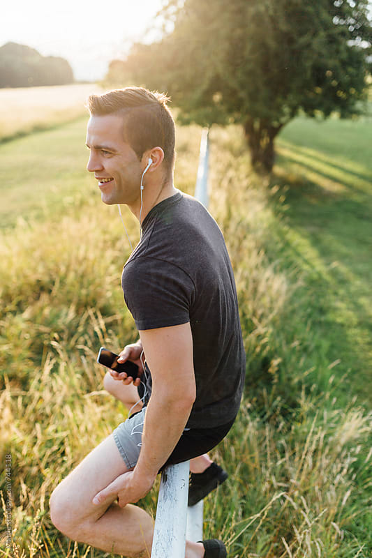 Sport Man Listening Music to the Mobile Phone in the Park by Mattia Pelizzari for Stocksy United