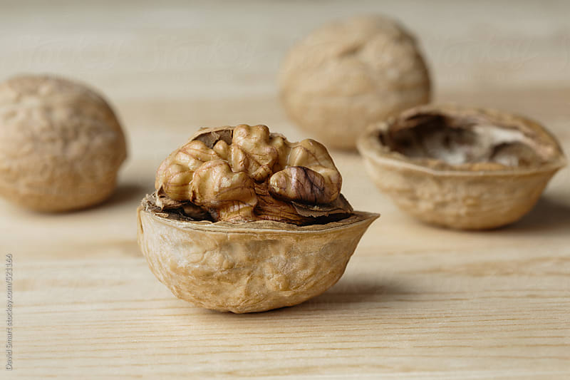 Close-up of walnuts on wooden background by David Smart for Stocksy United