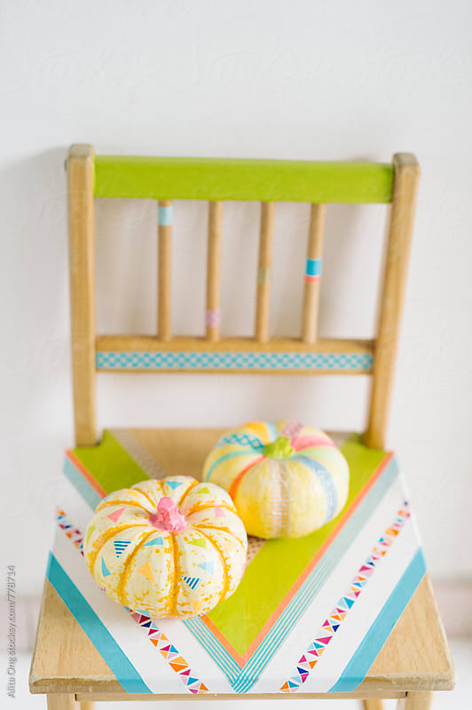 Washi taped pumpkins on a chair by Alita Ong for Stocksy United