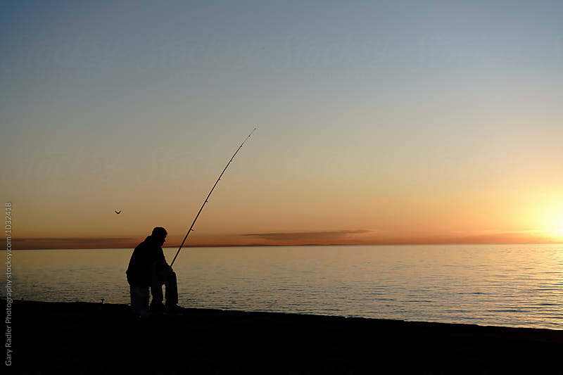 Silhouetted Angler on a Pier at Sunset by Gary Radler Photography for Stocksy United