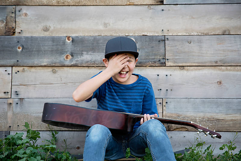 Asian boy holding his guitar and laughing by Curtis Kim for Stocksy United