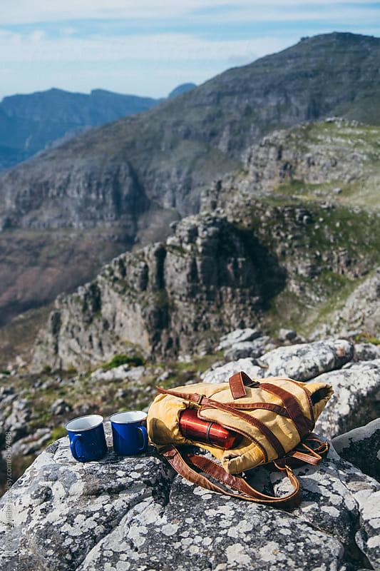 worn hikers backpack with flask and two coffee mugs on a mountain summit by Micky Wiswedel for Stocksy United