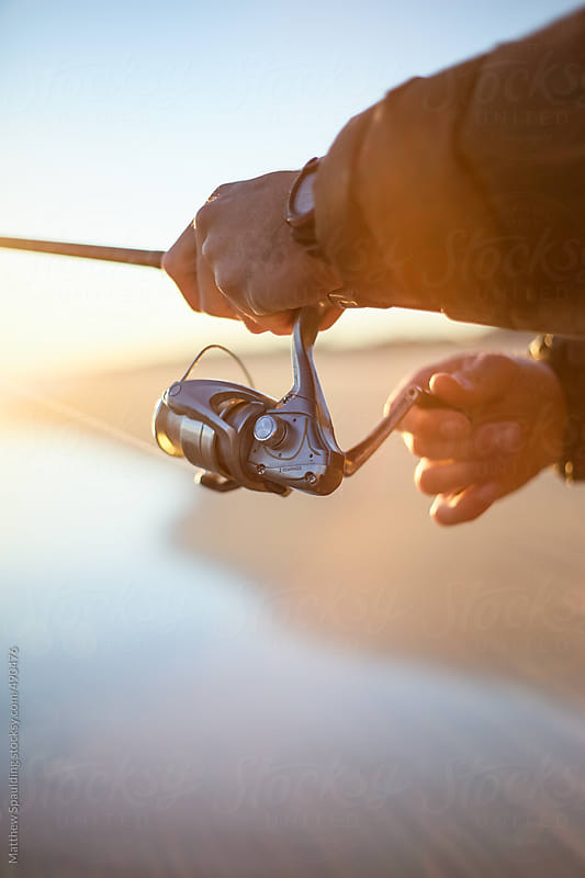 Man hands holding fishing reel and relaxing in sun by Matthew Spaulding for Stocksy United