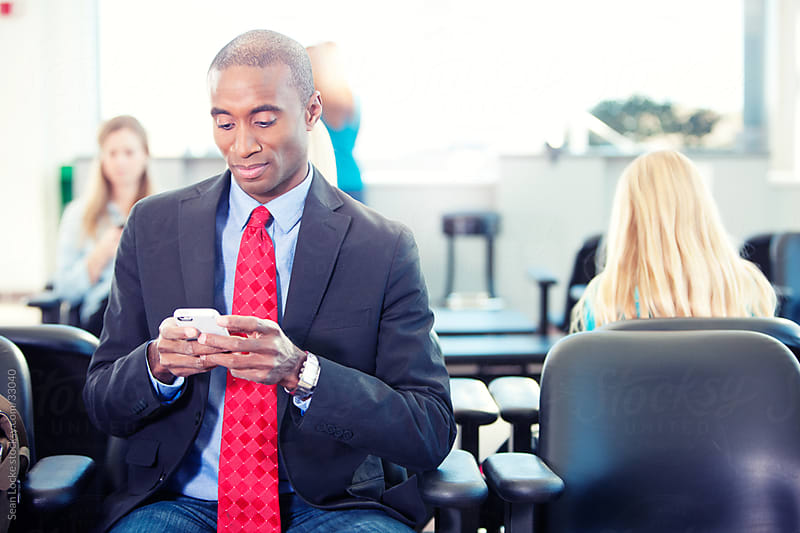 Airport: Businessman Texts from Waiting Area by Sean Locke for Stocksy United