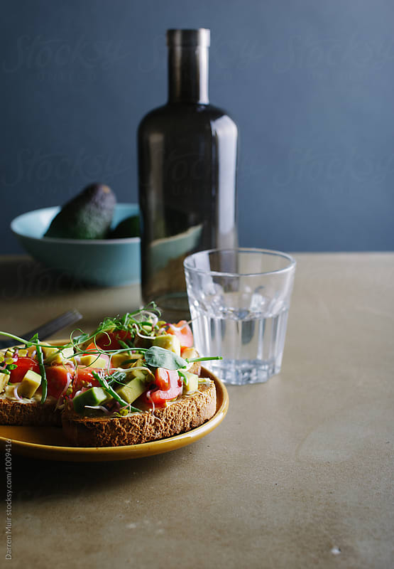Avocado,tomato and samphire toasts on a plate.Brunch and a glass of water, by Darren Muir for Stocksy United
