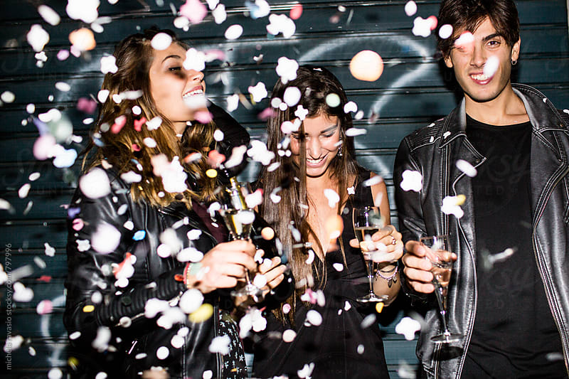 Group of friends celebrating together with champagne and confetti by michela ravasio for Stocksy United