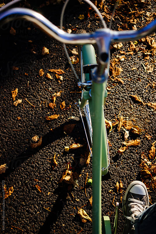 Riding a bicycle through autumnal leaves by Kirstin Mckee for Stocksy United