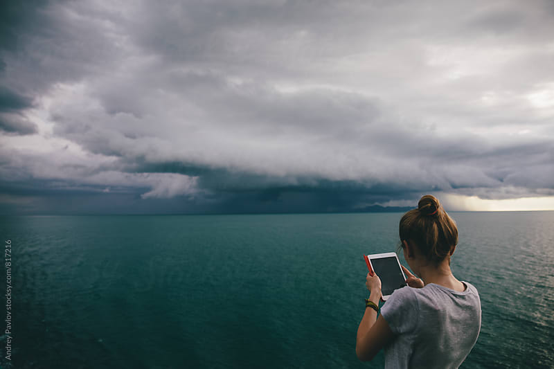 Woman taking photo of stormy seascape by Andrey Pavlov for Stocksy United
