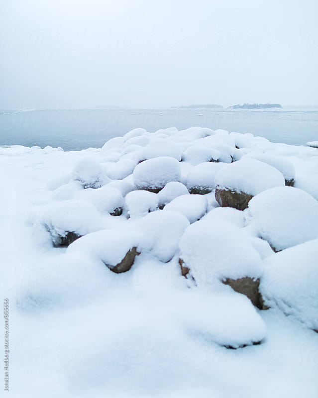 Fresh snow on a rocky shoreline by Jonatan Hedberg for Stocksy United