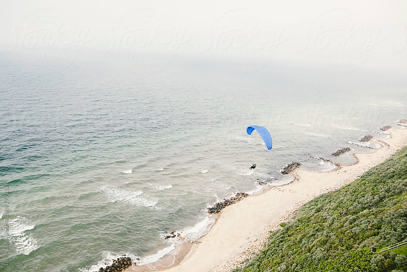 Paraglider flying over the coast by Lior + Lone for Stocksy United