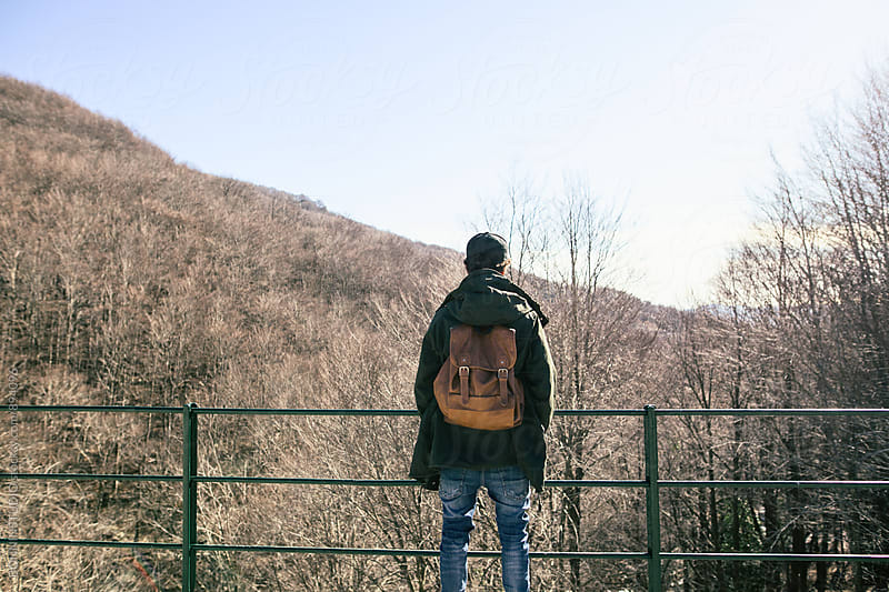 Back view of a mountaineer standing on bridge. by BONNINSTUDIO for Stocksy United