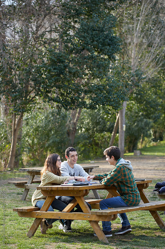 Group of three students in a relaxed moment in the campus by Miquel Llonch for Stocksy United