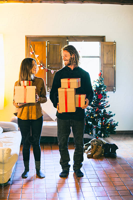 Young couple holding Christmas presents in a rural home. by BONNINSTUDIO for Stocksy United