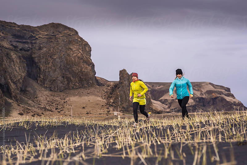 Two female runners in nature outdoors by Søren Egeberg Photography for Stocksy United